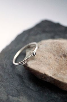 Silver skinny ring with black or grey diamond.