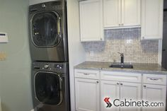 Compact laundry room with plenty of cabinet storage and a sink. #laundryroom