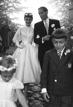 AUDREY HEPBURN A decidedly elfin tea-length, chiffon-sleeved Balmain for her wedding to co-star Mel Ferrer later that year. A wreath of fresh flowers completed the magical effect.