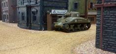 43: Der M4A1 Sherman hat die Straßenkreuzung im Ort erreicht. Er zieht ganz dicht an die eine Häuserwand, um nicht ein größeres Ziel abzugeben als nötig. Die Zeitungen sind leider nicht aktuell...