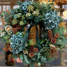 Handmade Christmas Wreath on the Door of our Chelsea Green London Florist.  Made with scented foliage including fur and eucalyptus, pine cones, berries and lime segments.  We can deliver hand made wreaths to anywhere in London the same day from our London Florist. Find out more via our blog or go to realflowers.co.uk