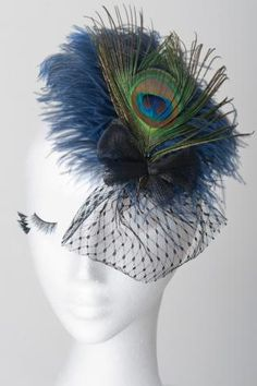 Fascinator of blue feather base, comb fastening, with peacock feather, crin bow and veil accent. Perfect Ladies hat and fascinator racewear fashion statement