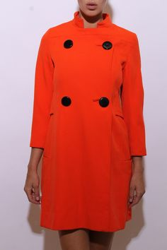 This vintage 1960s coat is made of bright orange wool, with oversized glossy black double breasted button closure.  #1960s #vintagecoat #btmvintage Shop now at: www.btmvintage.com