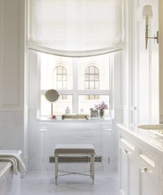 The light, airy master bath seems to float above the city. The embroidered, diaphanous Roman shade filters the light and softens the white marble.