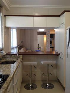 Cozinha pequena integrada à sala de estar e sala de jantar.
