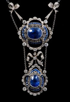 Fine early twentieth century Belle Époque sapphire and diamond necklace, the principle oval mixed cut cornflower blue sapphire in millegrain collet setting with a raised pierced gallery and a border of calibre cut blue sapphires, within a quatrefoil lobed open-work frame of old cut diamonds, with a diamond set bow suspending a further pear-shape pendant drop, similarly set with pear cut cornflower blue sapphire, all in millegrain setting. By Carrington & Co., 130 Regent Street, W.