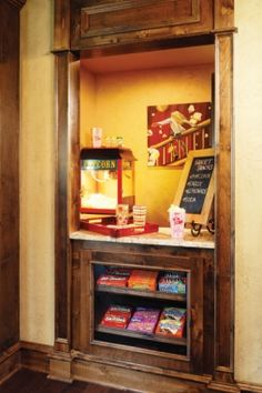Concession Stand  Originally designed as a ticket booth, the small room that sits outside the theater room is used as a concession stand. The glass-front cabinetry in the space showcases all of the family's favorite candy.