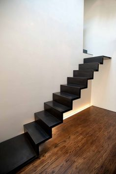 Blackened-steel stair floats from the wall. A water-jet cut system of structure is concealed in the thickness of the stair to pull off this impossible-looking feat.