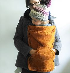 Keep your little one close and warm during the cold winter months with a knitted coat extender that buttons onto your existing coat.