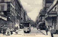 A sepia picture postcard of a commercial street scene looking down the street, showing a tramcar head-on. Some pedestrians mill about.
