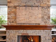 "These faux-painted sliding barn-wood ""doors"" provide a clever and stylish solution to concealing the TV when not in use.  Plus, the rustic look blends beautifully with this traditional living room's neutral color palette and doesn't overpower the lovely stone fireplace."