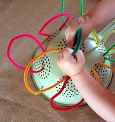 A metal colander, pipe cleaners and two small hands. A great fine motor and creative activity - Nurtured Learning Family Day Care.