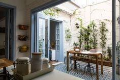 Decoração de apartamento pequeno paleta de cores em azul e branco. Na varanda mesa de madeira, plantas e cadeiras de ferro e madeira.