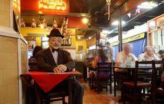 O famoso sambista Adoniran Barbosa é parte do cenário do restaurante Salada Paulistana, no Mercado Municipal de São Paulo, na Rua Cantareira.