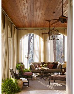"Flowing sheers soften the hard lines of the veranda's stucco, ""and they move beautifully in the wind."" The Royal iron daybed is from Century Furniture; the marble-topped iron tea table is from the Stalls; the lantern is from Circa Lighting."