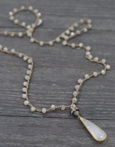 Hand beaded opalescent creamy colored crystal glass beads create the perfect preface for the most elegant gold plated faceted chalcedony drop pendant. Looks great layered with other Coastal Fog neckla