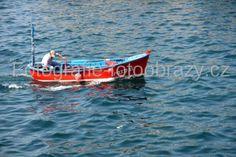 Červený člun na vlnách Atlantiku kdesi u španělského pobřeží.