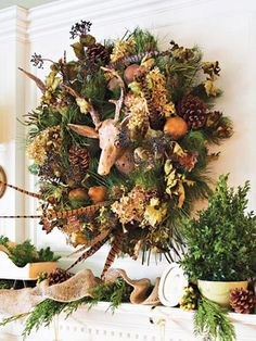 Dried hydrangeas and pheasant feathers dress up a pine wreath encircling the wooden deer head