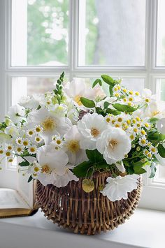 Combined with white snapdragons, miniature daisies and leafy greens, roses in full bloom billow from a woven basket.