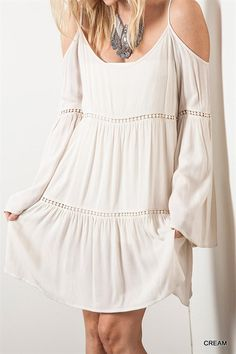 Cream Boho Babe Dress Unleash your inner boho babe in this gorgeous cream open shoulder dress. This color and style screams summer. Pom pom detailing across middle, bottom and sleeves.