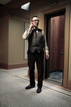 Finch (Michael Emerson) listening intently to his ear piece. Investigating the 'Person of Interest' (CBS).