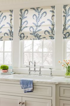 Lovely Roman Shades in this white kitchen   marble counters   blue and white   Perrin and Rowe faucet