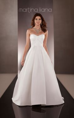 Discover this Martina Liana wedding dress featuring a natural waist, a twist sweetheart neckline, wide box pleating on the skirt and a traditional chapel train.