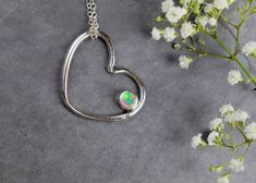 This beautiful pendant has been handmade with Sterling Silver wire that has been formed into a love heart.  The heart has the addition of a wonderful round Ethiopian Opal that is full of flash and colour.  The opal has been tube set within the heart.  The necklace is paired with a 925 sterling silver chain.