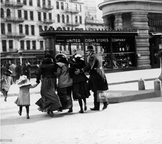 A uniformed New York City police officer assisting women and a small girl, across 5th Avenue, in front of the Flatiron (Fuller) building, c.1900. ~ {cwl} ~ (Getty Images)
