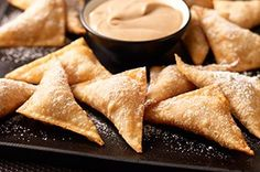 Pumpkin and cream cheese in wonton wrappers with caramel dip!    12  KRAFT Caramels  1tsp.  water  1/2cup  BREAKSTONE'S or KNUDSEN Sour Cream  1tsp.  ground cinnamon, divided  4oz.  (1/2 of 8-oz. pkg.) PHILADELPHIA Cream Cheese, softened  1/2cup  canned pumpkin  1Tbsp.  brown sugar  1tsp.  flour  1/4tsp.  orange zest  20  won ton wrappers  1  egg w