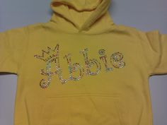 Abbie Hoodie, written in the bubbly Curlz font, with a pretty little crown. All done in the multi coloured rhinestuds to contrast with the sun yellow hoodie.We can make this design in any colour for you and apply it to a huge variety of garments. For more info/pictures you can visit our website or give us a call!