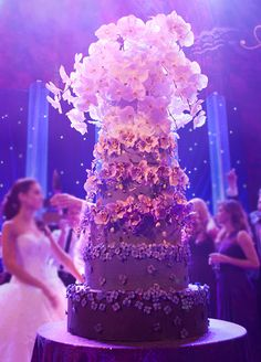 This 6 tier ombre purple wedding cake features hand-made sugar flowers and fresh white orchids cascading down from top.