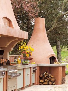 """This outdoor kitchen in Calistoga, California, takes its colors from the earth and the sky. A Viking warming drawer is conveniently closet to the Fogazzo 1050 pizza oven. """"It's all about entertaining,"""" architect Michael Layne says. """"People are going to gather where cooking's going on, so you need lots of counter space and plenty of seating - the open kitchen is bracketed on one end by the pizza oven and the other by a 30-foot horseshoe-shaped banquette."""""""