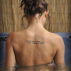 """Pequeño tatuaje en la espalda que dice """"I'm the hero of this story. I don't need to be saved"""", frase en inglés que significa """"Yo soy el héroe de esta historia. No necesito que me salven""""."""