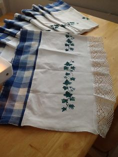 Making curtains of old bedsheet and table cloth. Only the lace is new. Hand printed green leaves.
