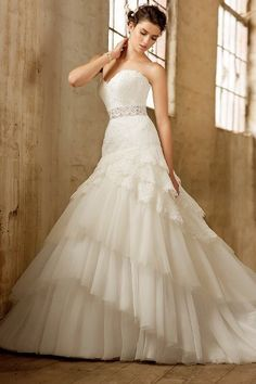 Lace and Tulle Aline gown.  Dropped waist bodice features beaded sweetheart neckline.  Full skirt is accented with layers of cut tulle.  Detachable beaded belt included.