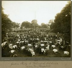 Dollis Hill house garden party, 1915.  From Brent Museum.  View across gardens taken from an elevated position ...  Tables and chairs in the foreground at which are seated soldiers from war hospitals in Willesden, ladies in fancy hats and dignitaries including a gentleman in the centre front. There are also a number of nurses. At the back are more people standing, and the charabancs and cars which brought the guests are lined up along the rustic fence which encloses the lawn.