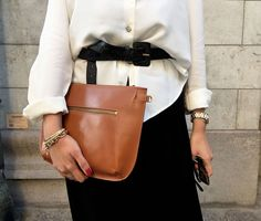 White blouse, black belt and skirt, tan leather clutch and gold accessories.