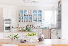 Fro Dering Hall this designer updated her kitchen by removing all the upper cabinets. Created a dining hutch effect and added windows. Really opened this space up.