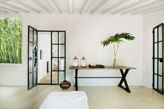 All-white room with console table and large palm leaves