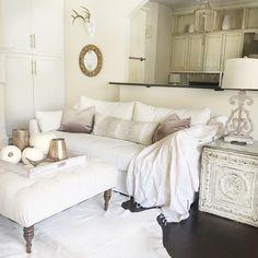 Ikea sofa. Farlov sofa. Slipcovered sofa. Neutral living room. Antelope print. Cowhide rug. Dark wood floors. Diy side table. Living room decor. Tufted Ottoman. Living Room paint color. White living room.