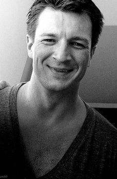 Nathan Fillion black and white smiling