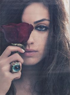 Messy and fills the frame. Natural beauty comparing to a flower. The ring is interesting. If you look at it closer it kind of reminds me of an eye. I feel that the photographer planned it to symbolize her eye behind the flower.