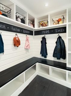 Stunning black and white mudroom features a glossy black l-shaped bench placed atop white shoe shelves and against a white shiplap trim finished with oil rubbed bronze assigned coat hooks fixed beneath a chalkboard border mounted under overhead shelves holding vintage metal bins.