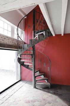 DH84 - SPIR'DÉCO® Art Déco. Escalier hélicoïdal d'intérieur métal et bois pour une décoration Art Déco. Marches + plateau bois incrustés, contremarches ajourées. Rampe à l'ancienne avec barreaudage de style Art Déco + option main courante en fer plat martelé. Finition : acier brut patiné. - Modèle déposé - © Photo : Nicolas GRANDMAISON