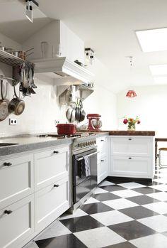Klassieke zwart wit tegels in de keuken. Een mooie witte landelijke keuken voorzien van paneel lades en klassieke schouw. De zwart wit tegels zien we vaak terug komen in landelijke en nostalgische keukens. Het terrazzo werkblad is op de kopse kant gecombineerd met een houten werkblad. Keukencentrum Schoonhoven