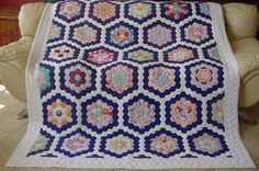 """A 2-generation Grandmas' Flower Garden quilt which began as 1930/1940's quilt blocks and was finished in the last quarter of the 20th century.  The gardens have many prints and solids, including some sear sucker fabrics, and are surrounded by navy and white paths.  The quilt measures 80"""" x 68"""".  Love the navy blue and white surrounding the vintage fabrics."""