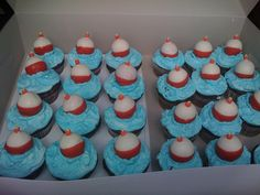"Cupcakes with Cake Ball Bobbers - My grandson really wanted a fishing theme for his 7th birthday classroom celebration. I made triple chocolate cupcakes with buttercream ""water"". Bobbers are strawberry cake balls dipped in white chocolate (double dipped to cover the pink of the strawberry), then the bottom half dipped in red chocolate. The tops of the bobbers are gumpaste."