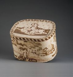 "EARLY AMERICAN WALLPAPER-COVERED BAND BOX. The sides depicting landscape views, the cover two puppies. Height 10"", length 19"""