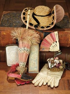 "8"" (20 cm.) l. parasol. Including silk fringed French parasol with carved bone handle and loop belt ring; woven French bonnet known as ""A Deux Bonjours"" with rose silk lining, and black velvet trim, French carved bone folding fan with rose silk detail, and original fancy box; gilt metal basket with flowers, mother-of-pearl purse with carved detail, kidskin gloves, and a Viennese dance card in the shape of a book and slipper, and with original pencil and silk cord and tassel. Overall…"